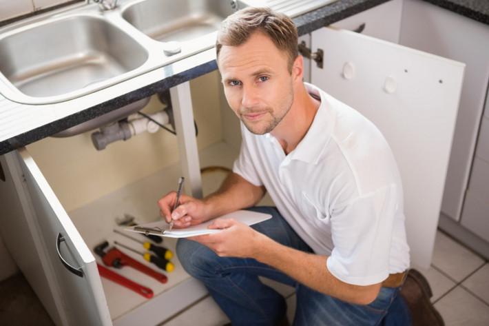 sydney plumber working under a sink